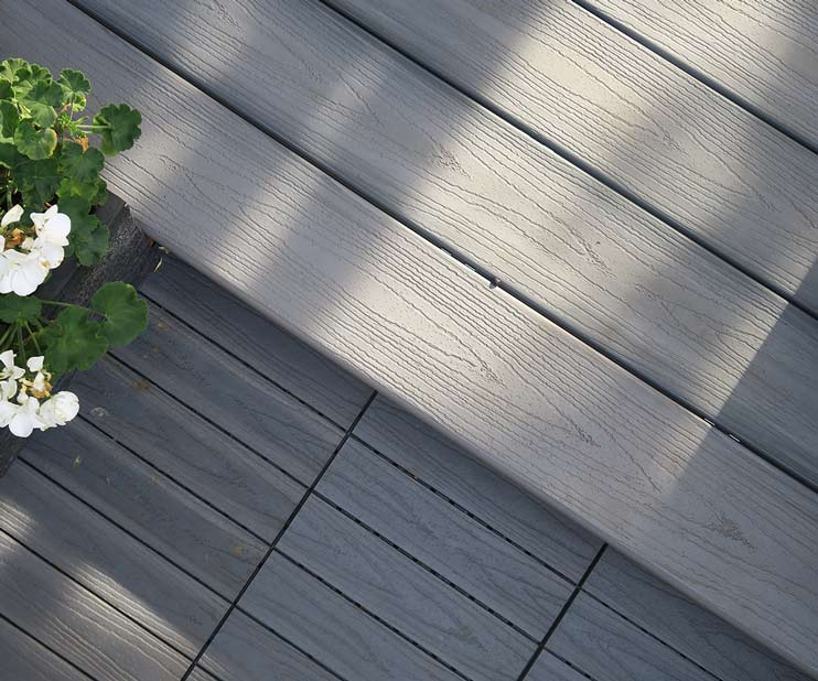 combination between deck tiles and deck boards to create levels - composite decking in light grey colour with a finishing board